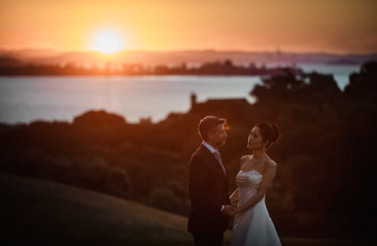 Couple by the sea at the sunset in New Zealand